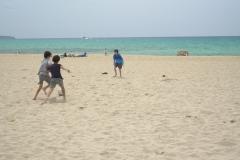 Jungs spielen Fussball am Strand